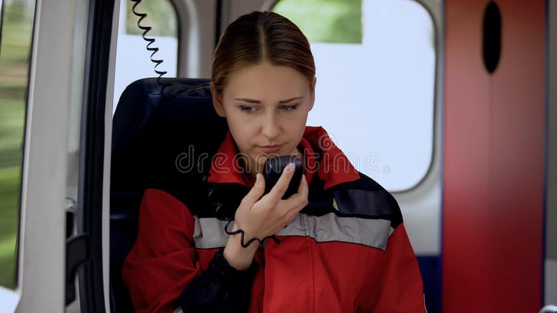 Female paramedic talking by radio in ambulance, ready to drive out on call. Stock photo royalty free stock photos