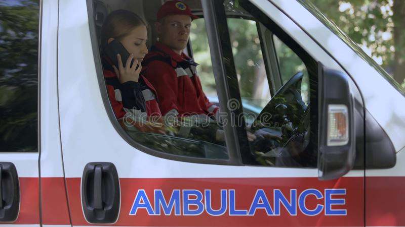 Female paramedic using smartphone to call patient, ambulance crew on-duty. Stock photo royalty free stock photography