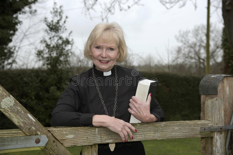 Female parish priest on a house call entering the garden gate. Elderly woman vicar leaning on a garden gate stock photography