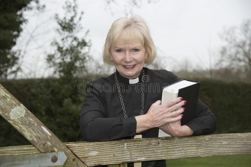 Female parish priest on a house call entering the garden gate. Elderly woman vicar leaning on a garden gate stock image