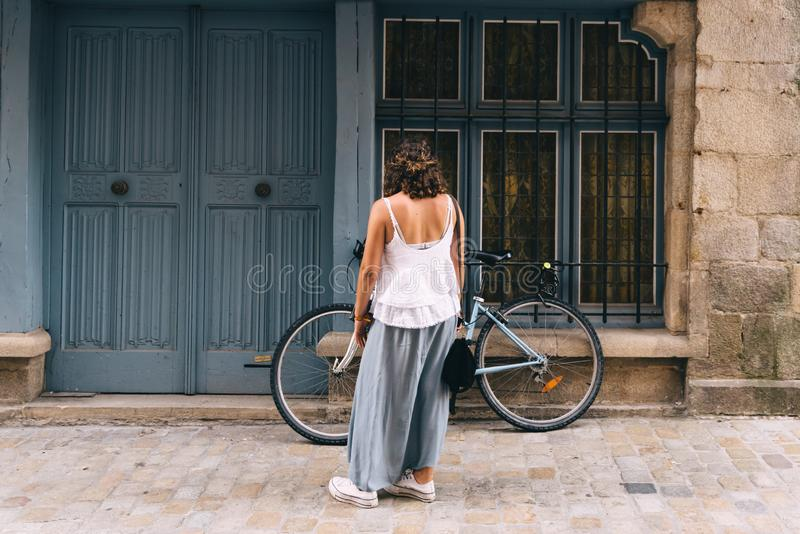 Female parking the bicycle at old house door royalty free stock images