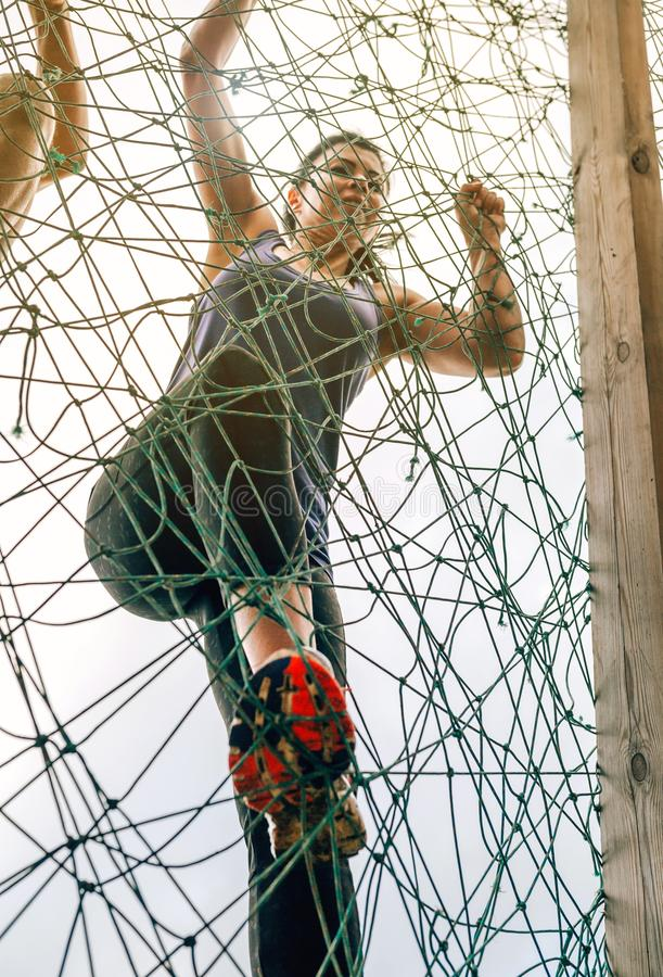 Participant in obstacle course climbing net. Female participant in an obstacle course climbing a net stock images