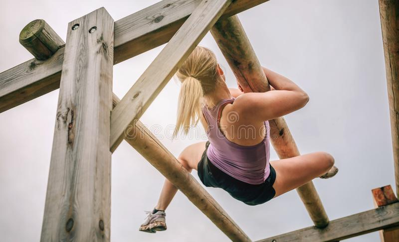 Participant in a obstacle course doing weaver. Female participant in a obstacle course doing weaver obstacle royalty free stock images