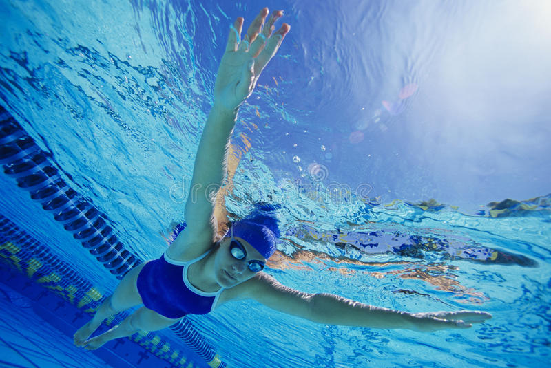 Female Participant Swimming Underwater. Middle aged female participant swimming under water in a swimming race royalty free stock images