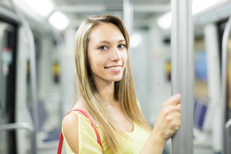 Female passanger in train of metro. Casual smiling female passanger in train of metro royalty free stock photography
