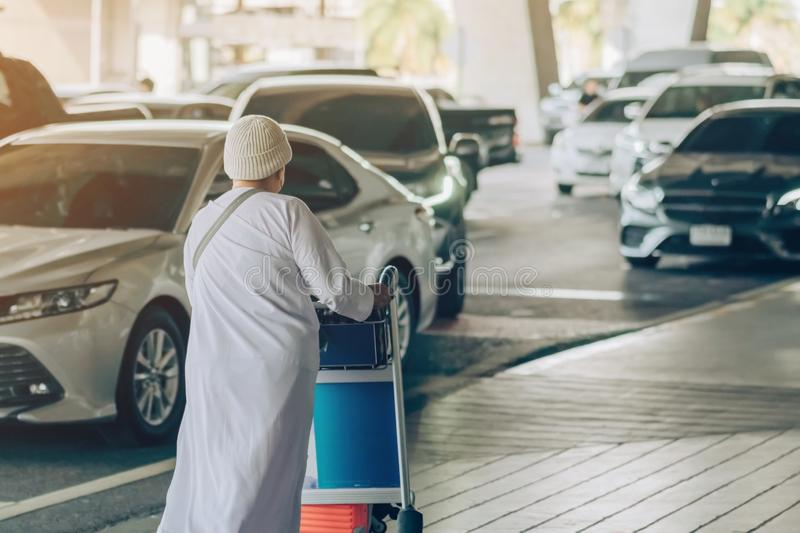 Female Passenger with big roller luggage walk to wait for the car to pick up stock image