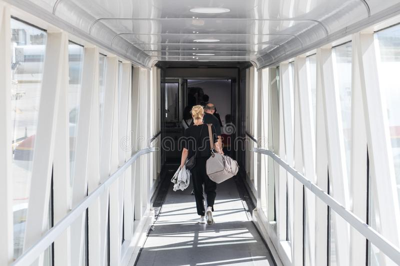 Female passenger carrying the hand luggage bag, walking the airplane boarding corridor. Airplane Boarding. Casual female passenger carrying the hand luggage bag stock photography