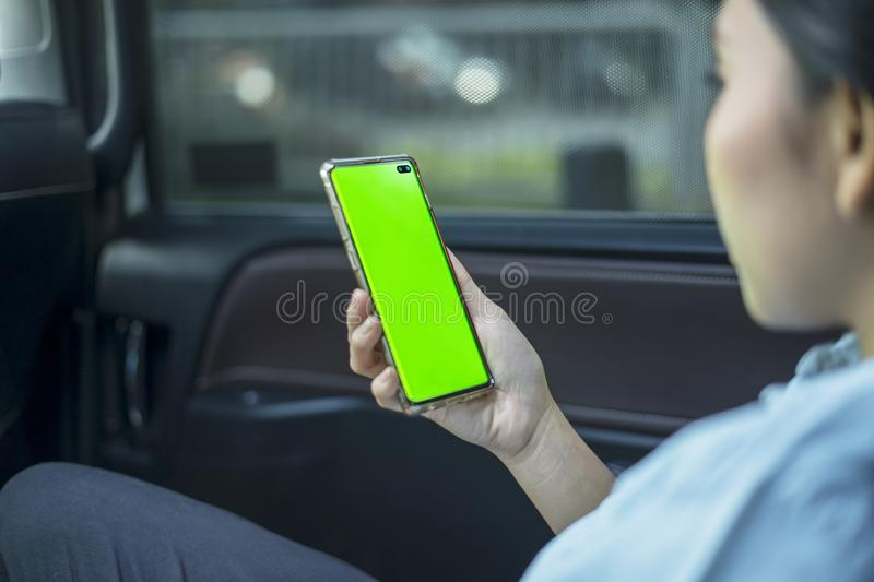 Female passenger using a phone with blank screen royalty free stock photo