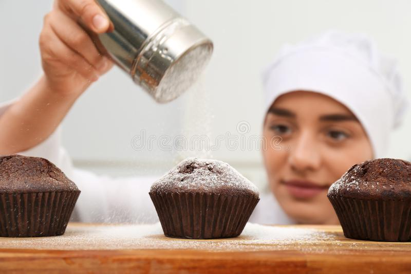 Female pastry chef sprinkling cupcakes with sugar powder. In kitchen stock photography