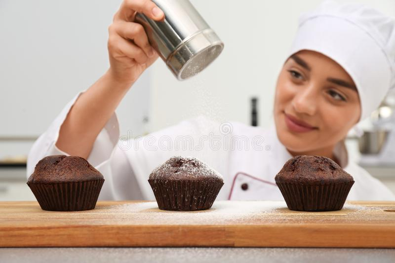 Female pastry chef sprinkling cupcakes with sugar powder. In kitchen royalty free stock photo