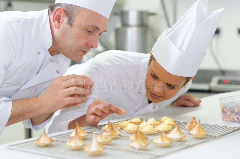 Female pastry intern putting topping on coconut macaron stock images