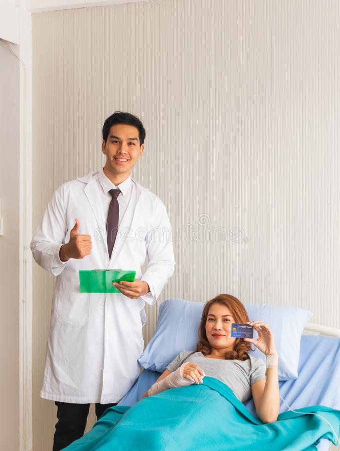 Female patient in the bed carried a credit card, with a young doctor standing there to support by the bed. The female patient in the bed carried a credit card royalty free stock image