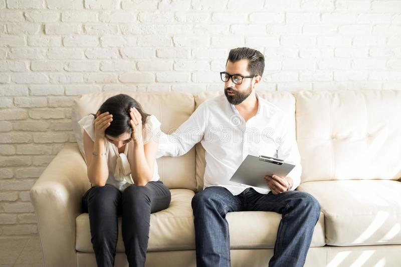 Concerned psychologist comforting depressed patient. Female patient crying while sitting on the sofa and therapist comforting her royalty free stock photography