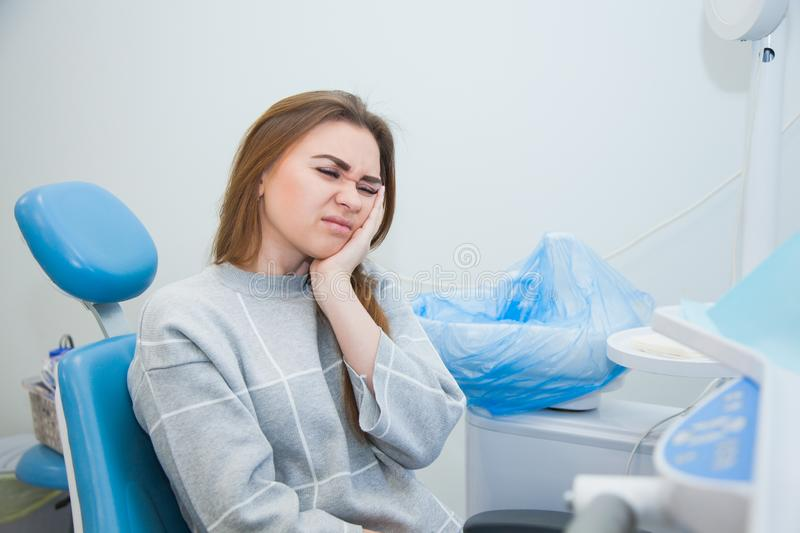 Female patient at dentist cabinet suffering from severe tooth ache. Young woman holding cheek sitting at stomatologist armchair royalty free stock photo