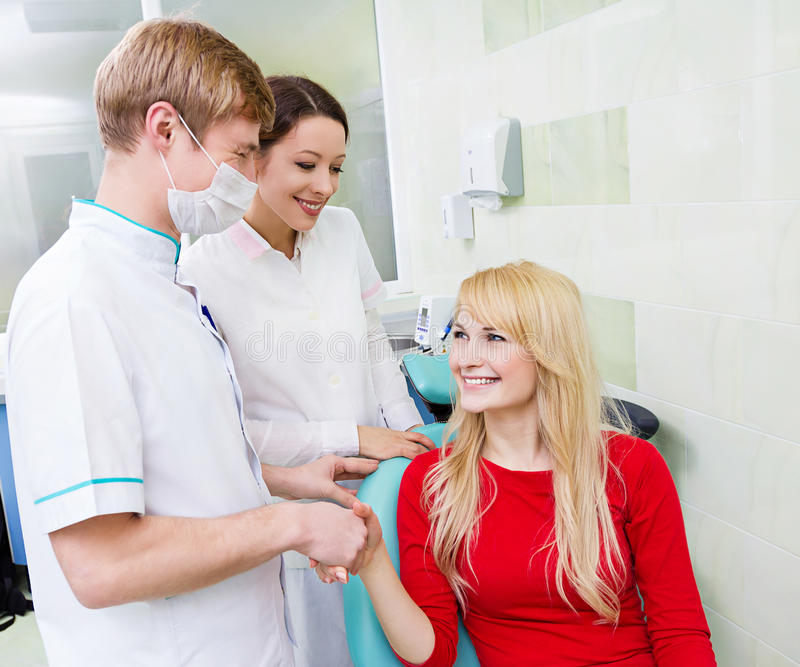 Female patient in dentist office, handshake with doctor stock image