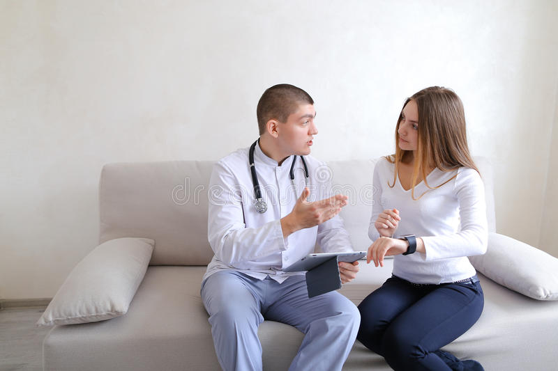 Female patient girl and male doctor osteopath with gadgets. Solv stock photography