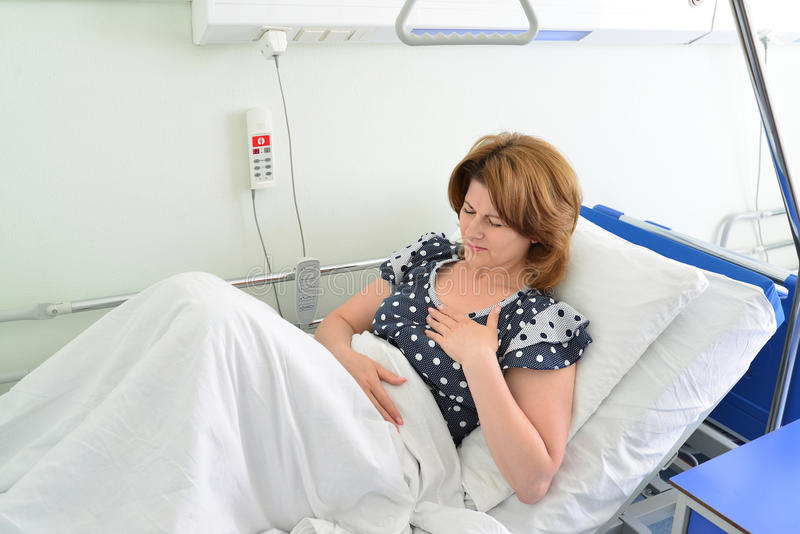 Female patient With heartfelt pain lying on bed in hospital ward. Female patient With heartfelt pain lying on a bed in hospital ward royalty free stock photography