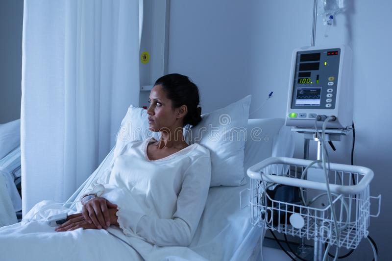 Female patient looking away while relaxing on bed of hospital royalty free stock photography