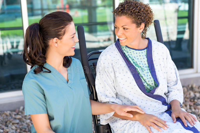 Female Patient Looking At Nurse While Sitting On stock photos