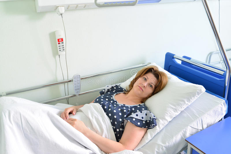 Female patient lying on bed in hospital ward. Female patient lying on a bed in hospital ward stock photo