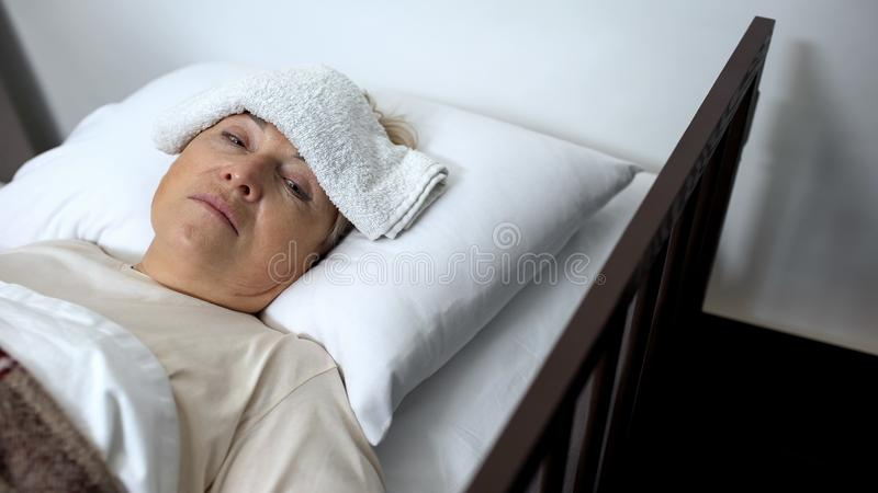 Female patient lying in sickbed with compress on forehead, influenza disease stock photos