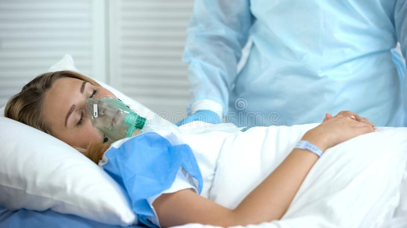 Female patient in oxygen mask sleeping, nurse standing by, surgery preparation royalty free stock image