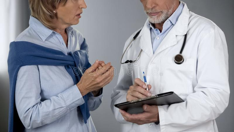 Female patient talking to doctor about test results, shocked by diagnosis royalty free stock photography