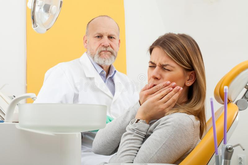 Female patient with toothache at the dentist office. Young female patient with severe toothache at the dentist office with elderly male dentist in the background royalty free stock photos