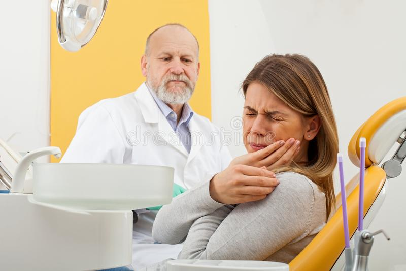 Female patient with toothache at the dentist office. Young female patient with severe toothache at the dentist office with elderly male dentist in the background stock images