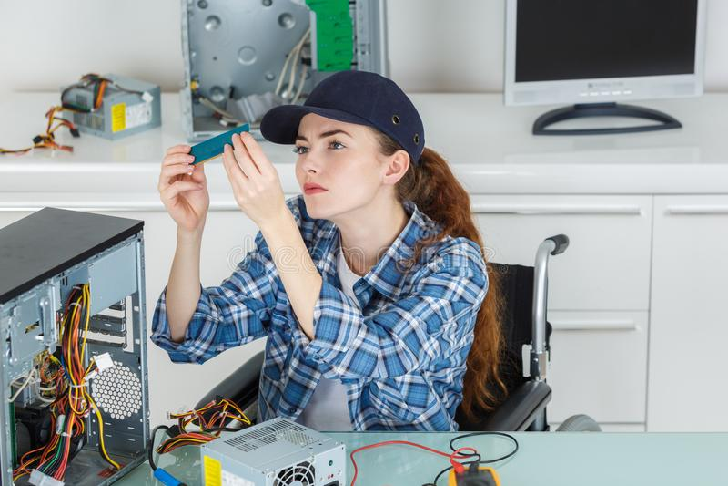Female pc technician checking pc parts stock photo