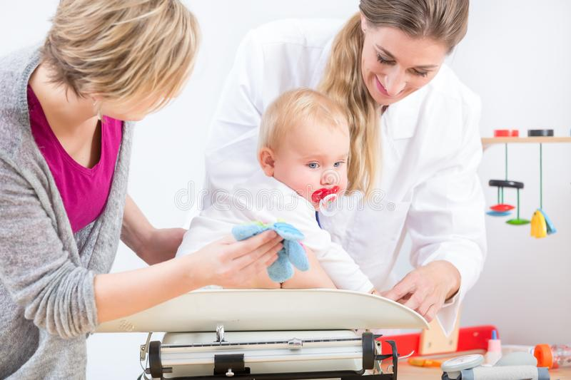 Pediatric care specialist smiling while measuring the weight of a baby girl royalty free stock image