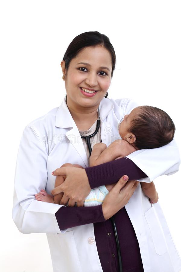 Female pediatrician holds newborn baby stock photo