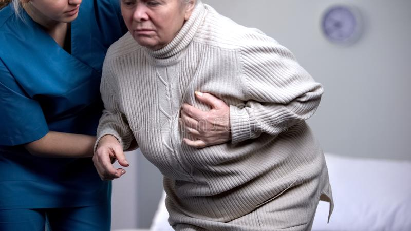 Female pensioner feeling sudden heart pain, nurse helping old patient, health stock photo