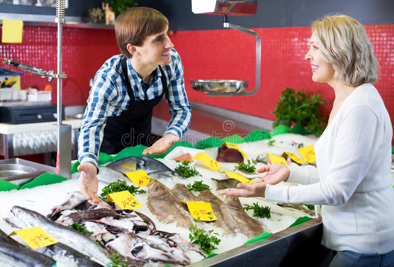 Female pensioner purchasing chilled on ice fish stock photos