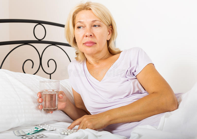 Female pensioner taking medicine. Before falling asleep in bed stock photos