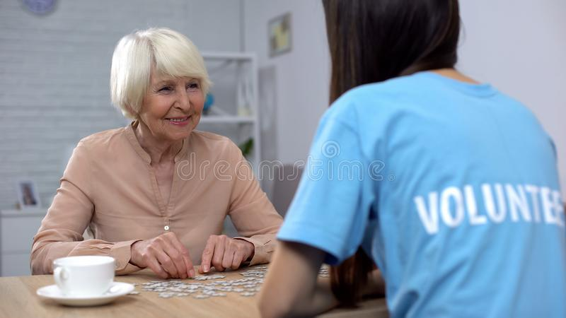 Female pensioner young volunteer putting puzzle together, old people attention stock images