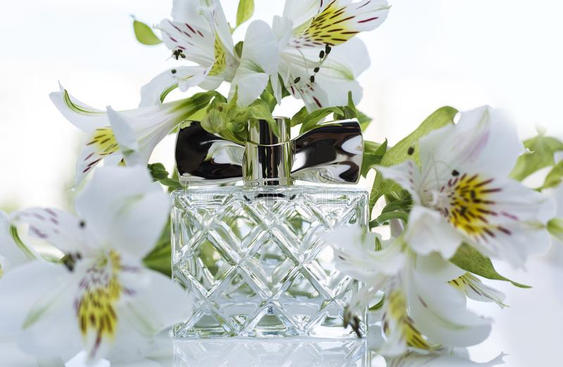 Bottle of perfume with white orchid stock images
