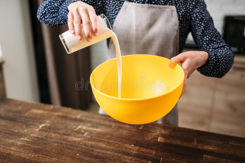 Female person adds cream into a bowl, cake cooking. Female person adds cream into a bowl, homemade cake cooking. Fresh tasty dough preparation stock photos