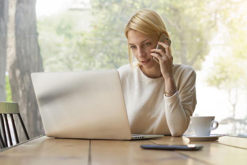 Female person busy working in modern office interior or coffee shop royalty free stock photos