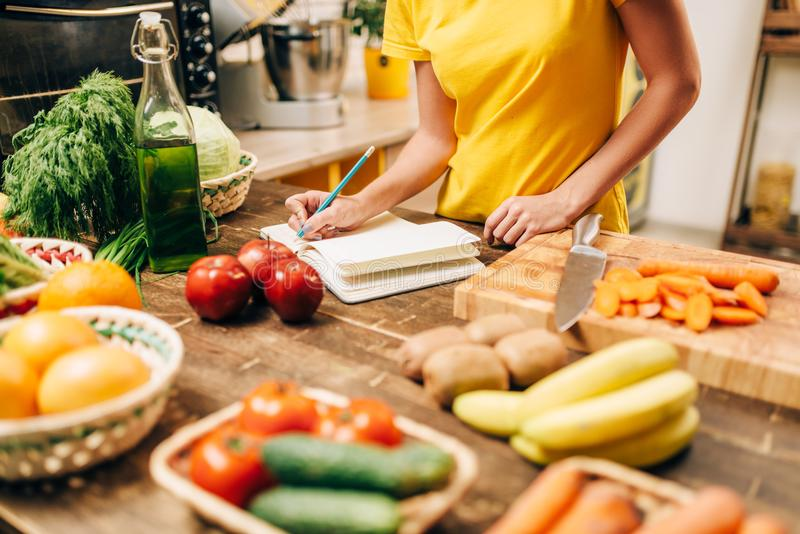 Female person cooking on the kitchen, bio food. Female person cooking on the kitchen, healthy bio food. Vegetarian diet, fresh vegetables and fruits on wooden stock images