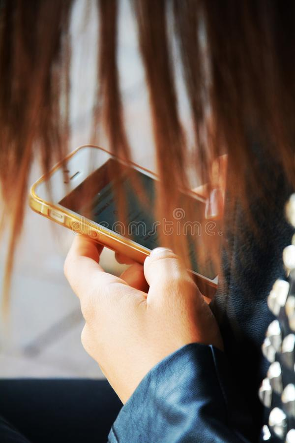 Female person holding a smartphone. Female person holding and watching a smartphone in a train station stock photography