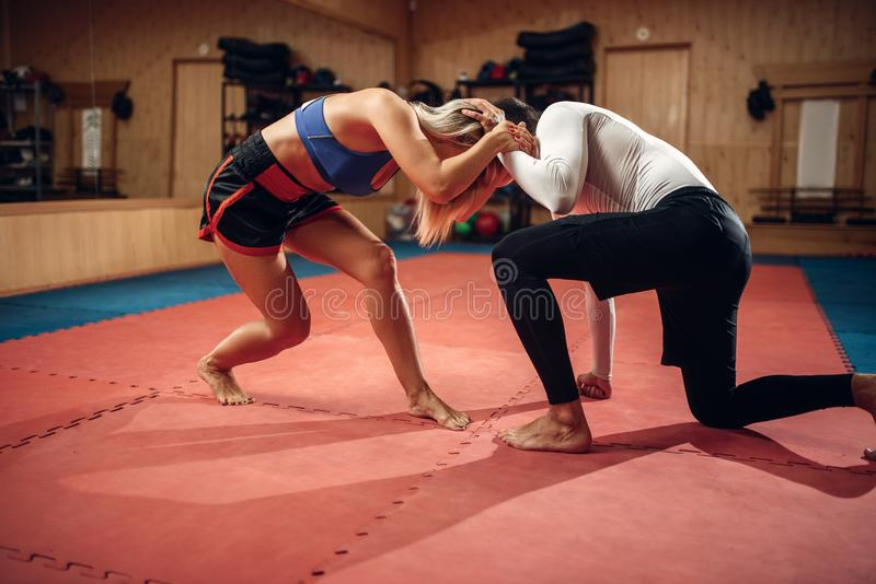 Female person holds the grip, self defense workout. With male personal trainer, gym interior on background. Woman on self-defense training royalty free stock photo