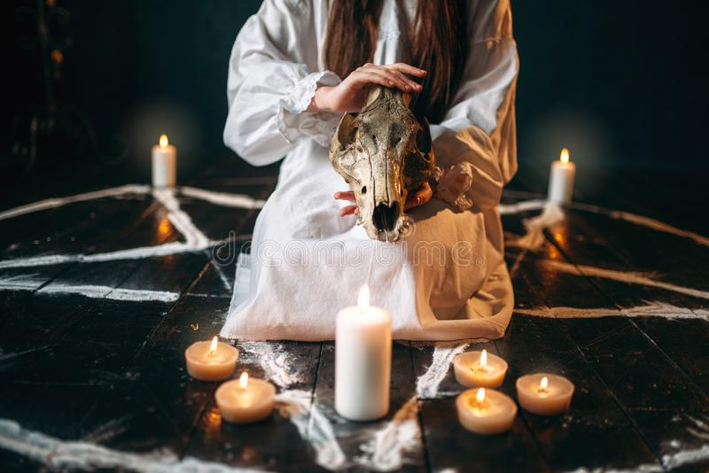 Female person holds skull in hands, magic ritual stock image