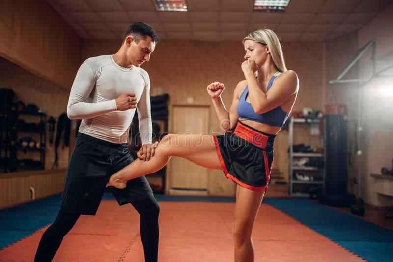 Female person makes kick in groin, self defense. Female person makes a kick in the groin, self defense workout with male personal trainer, gym interior on royalty free stock image
