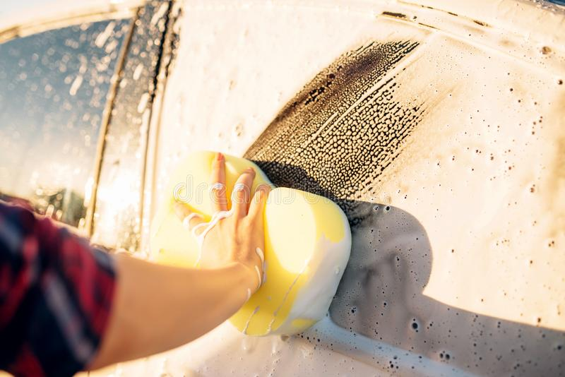 Female person scrubbing vehicle with foam royalty free stock images