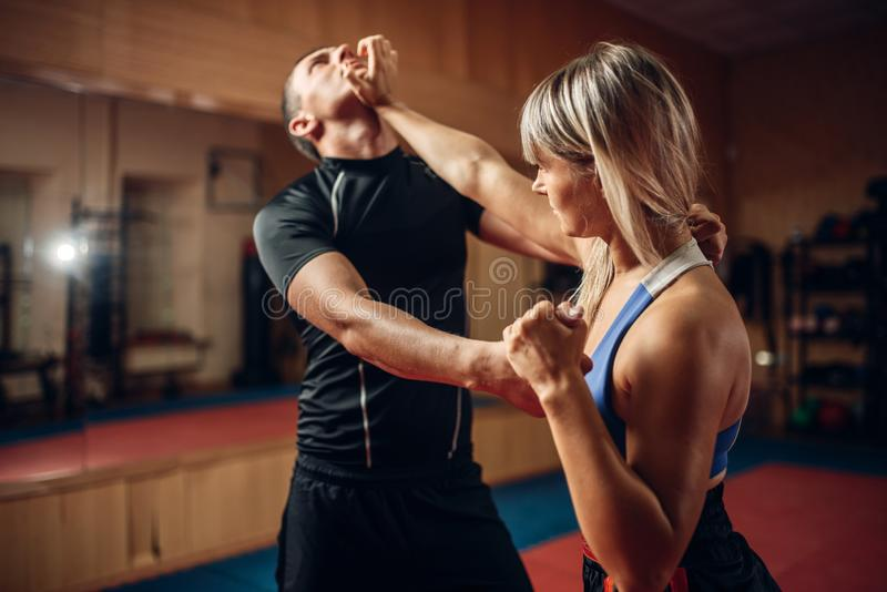 Female person on self-defense workout with trainer. Female person on self-defense workout with male personal trainer, gym interior on background. Woman makes stock photography