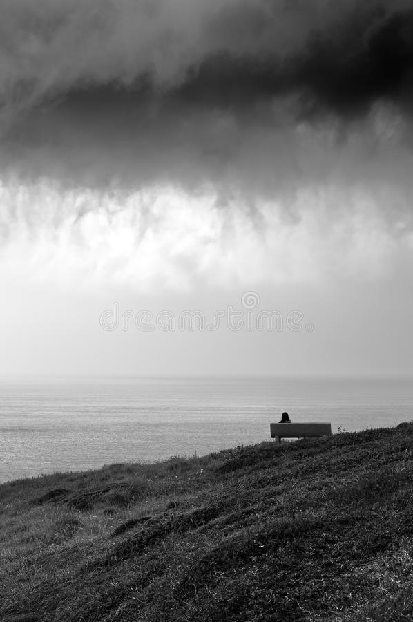 Female person sitting on bench looking sea. One and solitary female person sitting on bench and lookin at sea with stormy clouds stock photos