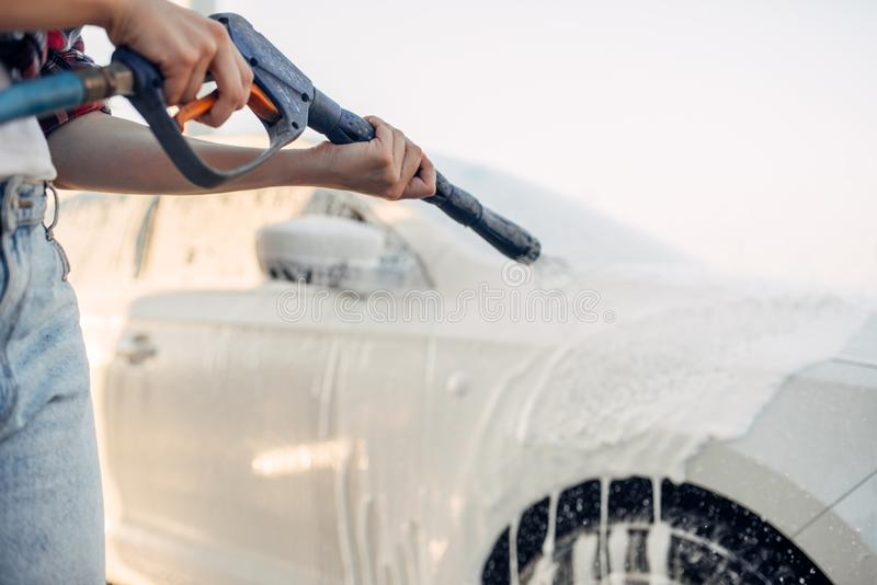 Female person wash off the foam from car royalty free stock image