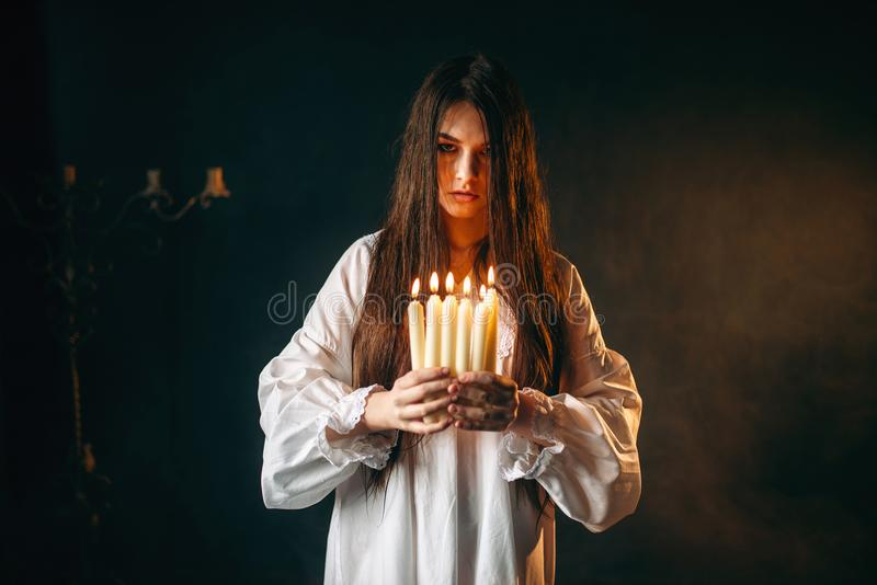 Female person holds candles in hands, divination. Female person in white shirt holds candles in hands. Dark magic ritual, occultism and exorcism, divination royalty free stock images