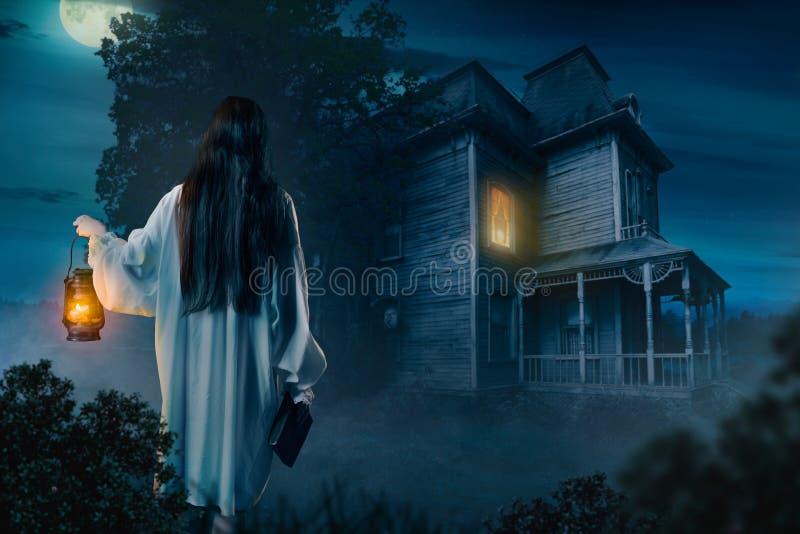 Female against abondoned house, moonlit night. Female person in white shirt holds kerosene lamp and spellbook in hand against abondoned house, moonlit night stock images